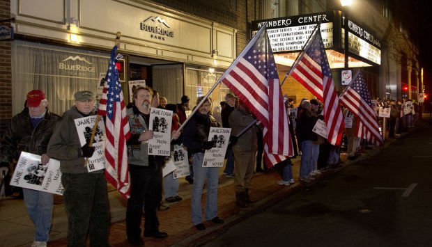 Demonstrators stand in protest of Fonda