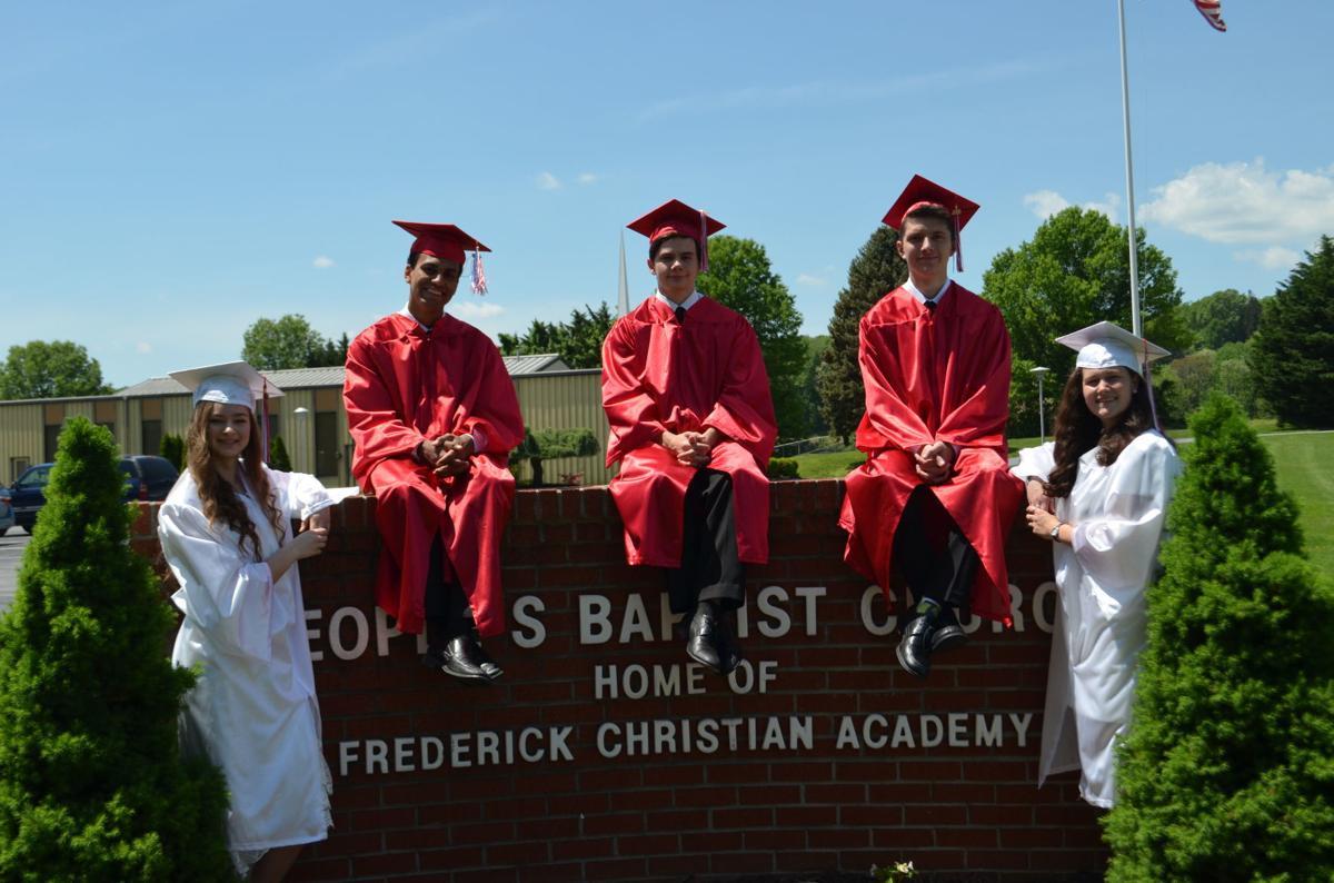 FCA graduates pose on sign
