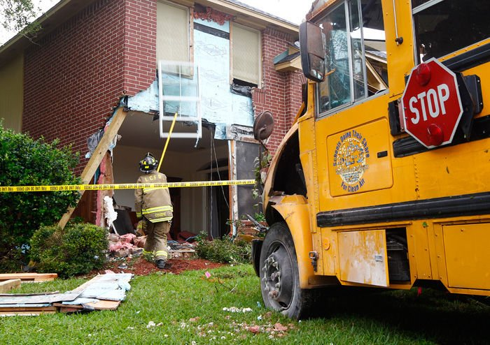 A League City firefighter works to stabilize debris after a Clear Creek ISD  special education bus was removed from the front of a house in the Oaks of  Clear ...