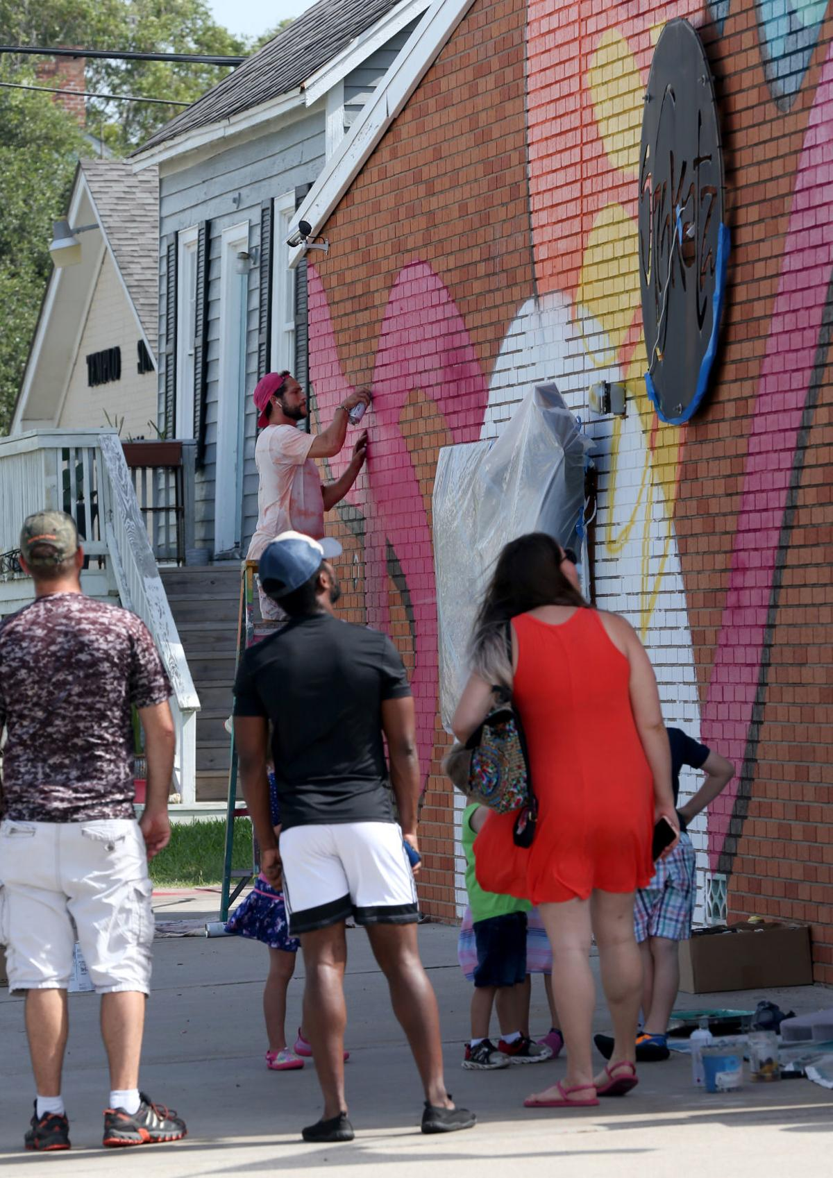 Artist paints mural on side of island restaurant