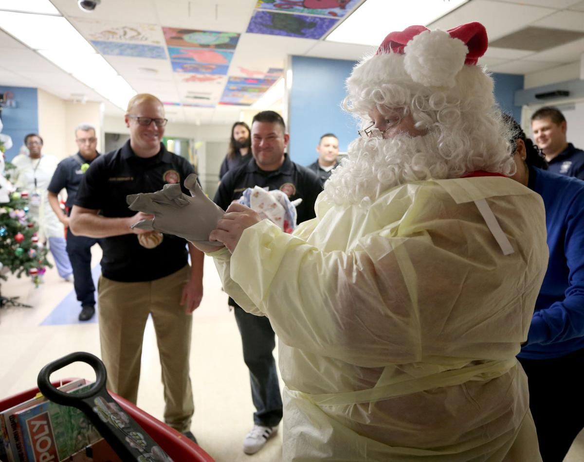 Santa Claus and firefighters deliver toys to young patients at UTMB