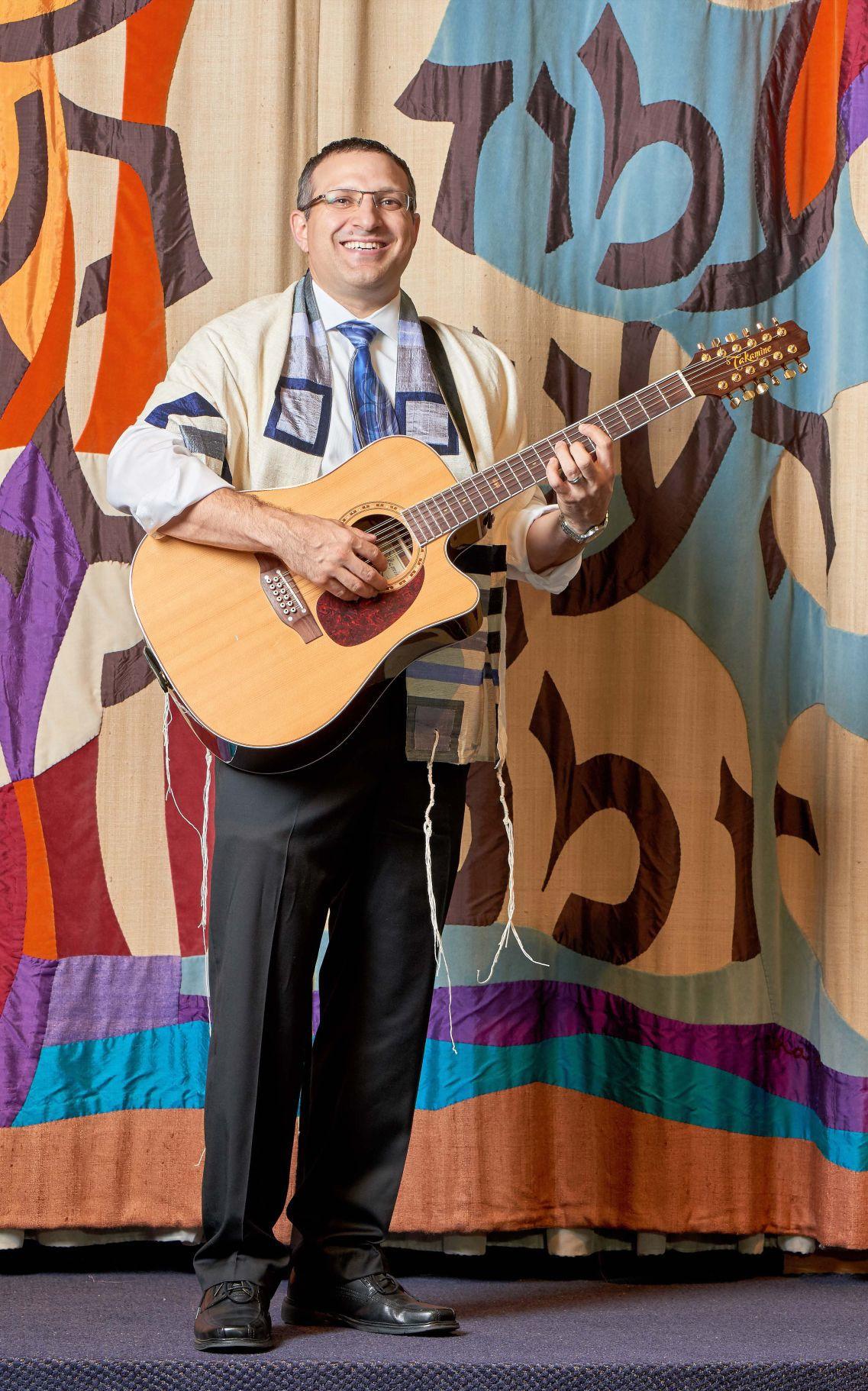 Rabbi Matt strumming his 12 string guitar.jpg
