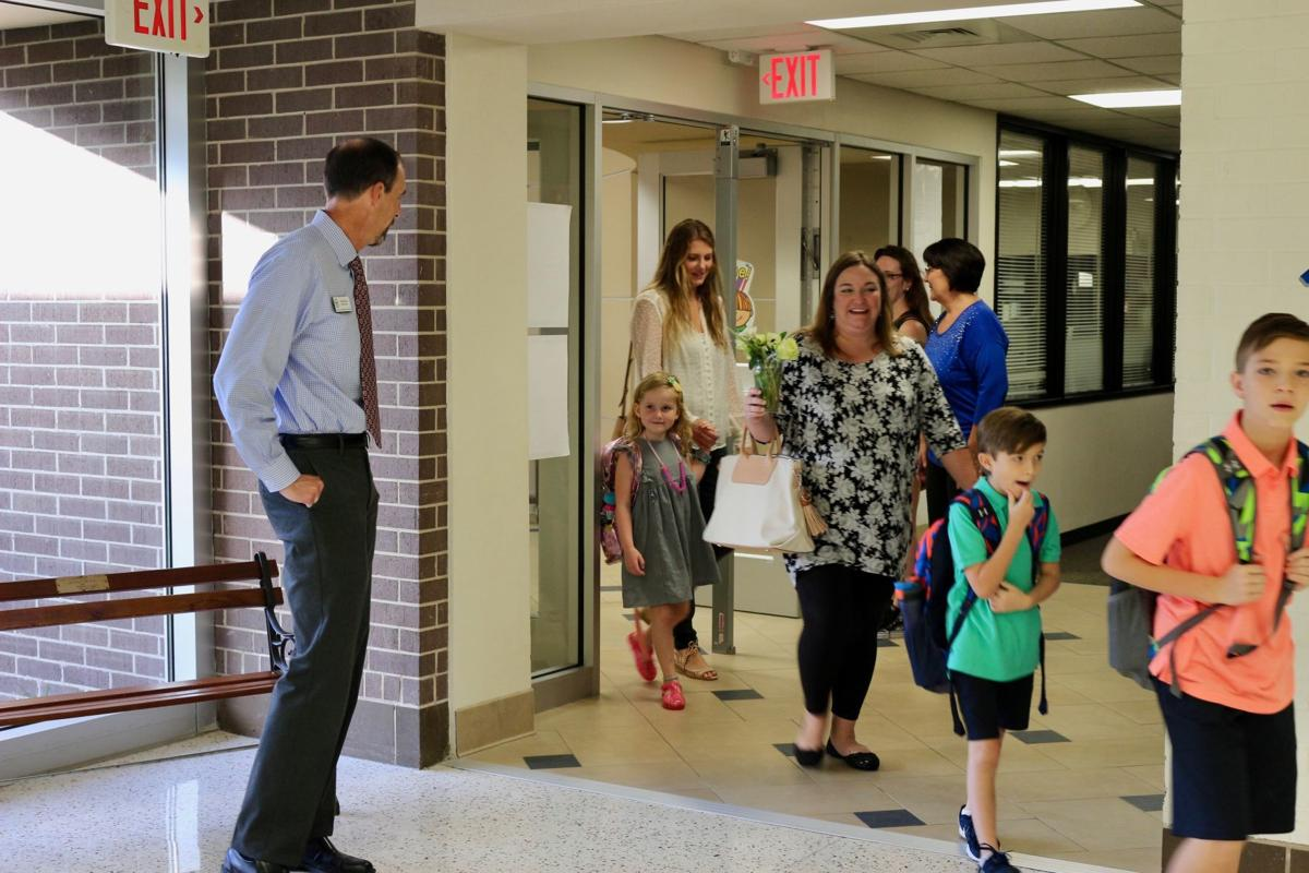 School officials at Westwood Elementary guide students to class