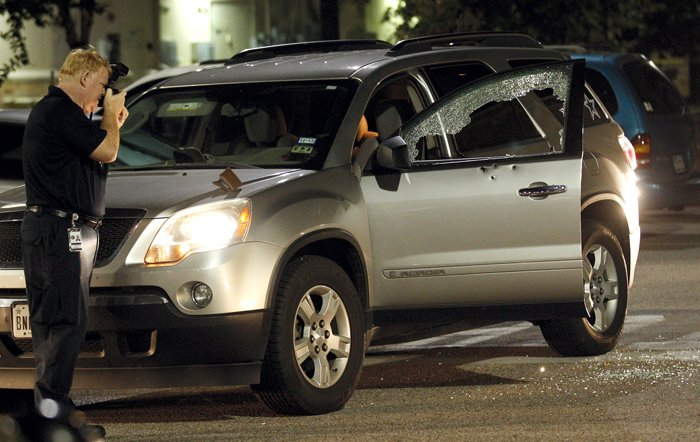 league city police forensics specialist eric richardson photographs bullet holes in an suv at the scene of a shooting in the walmart parking lot in victory