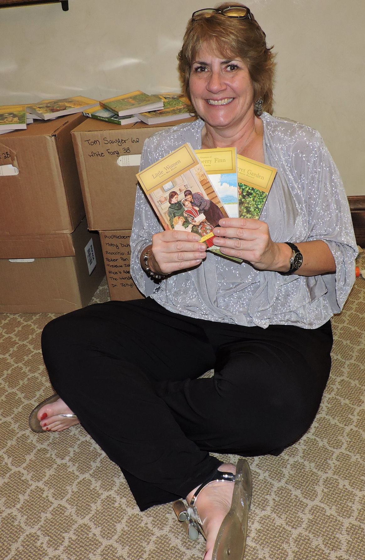 Tina Dewar holds some of the hundreds of classic books donated to Abrams Elementary School at Koats 4 Kids. 102116 Photo by Linda Navarro