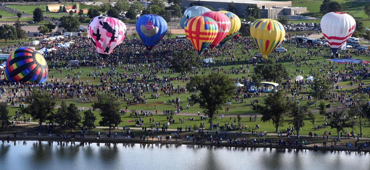 Thousands filled Memorial Park to watch the second day of the Colorado Balloon Classic on Sunday, August 31, 2014 in Colorado Springs, Colorado. The second wave of balloons inflates and spectators line the banks of Prospect Lake hoping to see dips in the lake. The photo was from the Something Borrowed balloon flown by pilot Clare Wade-Callihan. ONLINE PHOTO GALLERY (The Gazette/Jerilee Bennett)