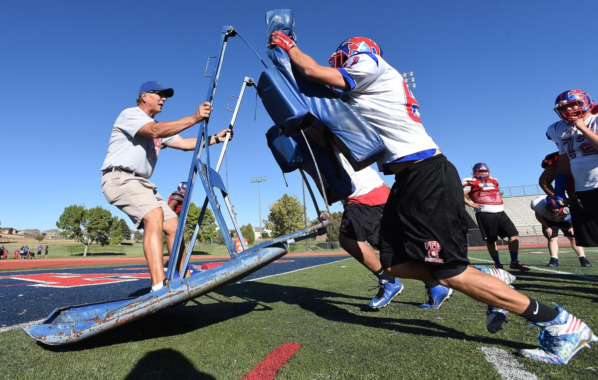 Longtime Fountain-Ft. Carson Coach Mitch Johnson coaches while being pushed around the field by football players on the two man sled during a practice at the high school on Tuesday, October 13, 2015. (Jerilee Bennett/The Gazette)
