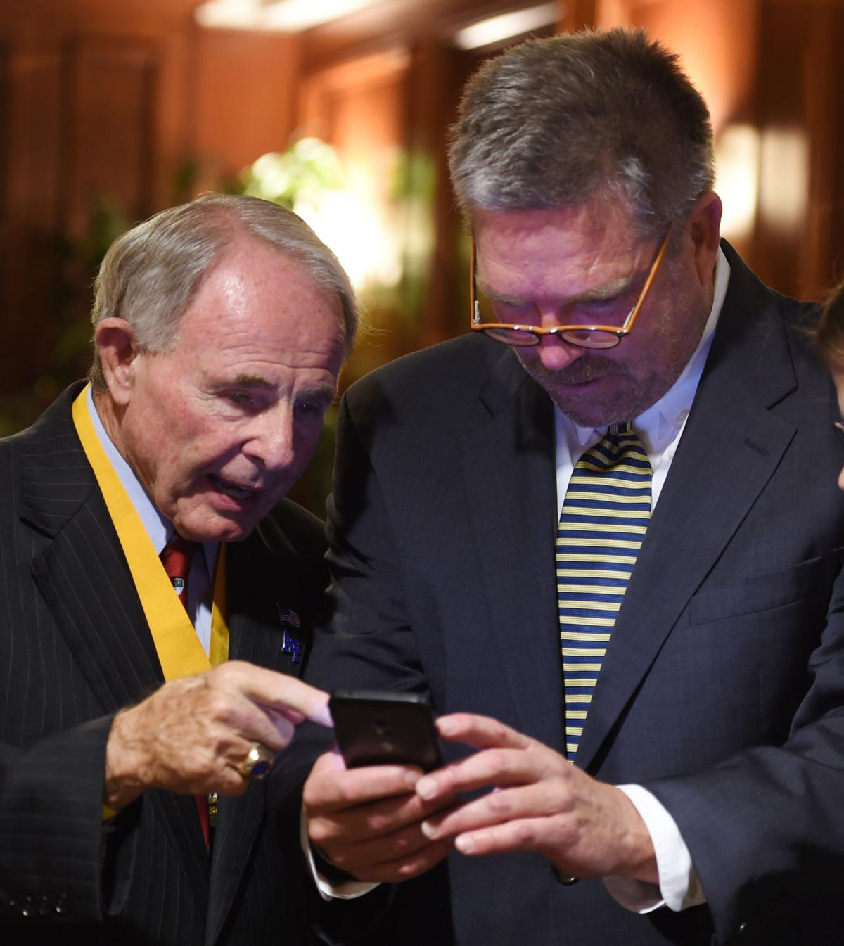 Air Force football coaching legend Fisher DeBerry shares some images on his phone with Tom Osborne, President & CEO of Colorado Springs Sports Corp. (Jerilee Bennett/The Gazette)