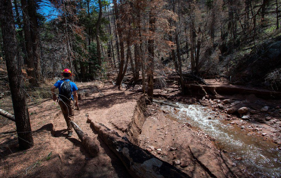 Joe Lavorini of Rocky Mountain Field Institute surveys the flood damge to the Waldo Canyon Trail just past the loop hiking clock wise Friday, May 1, 2015, in Waldo Canyon Trail area. The much of the trail in that area is wiped out from the flooding. (The Gazette, Christian Murdock)