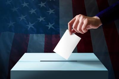 Election in America Concept. Hand Dropping a Ballot Card into the Vote Box, Flag of United States as background (copy)