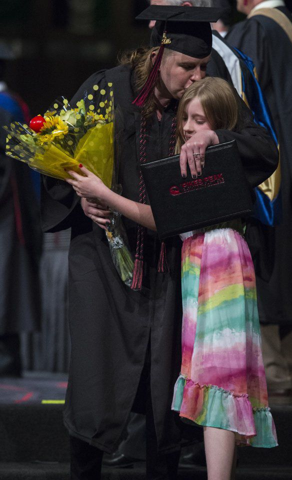 Jocelyn Andersen, 9, greets her mother, Pam Andersen, at the side of the stage with flowers and a hug after she received her diploma during the commencement ceremony for The Pikes Peak Community College class of 2016 May, 14, 2016, at New Life Church in Colorado Springs. See Gazette.com for photo galleries from 60 area graduations including Pikes Peak Community College. (The Gazette, Christian Murdock)