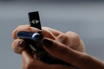 A woman holds a Juul e-cigarette while walking in New York