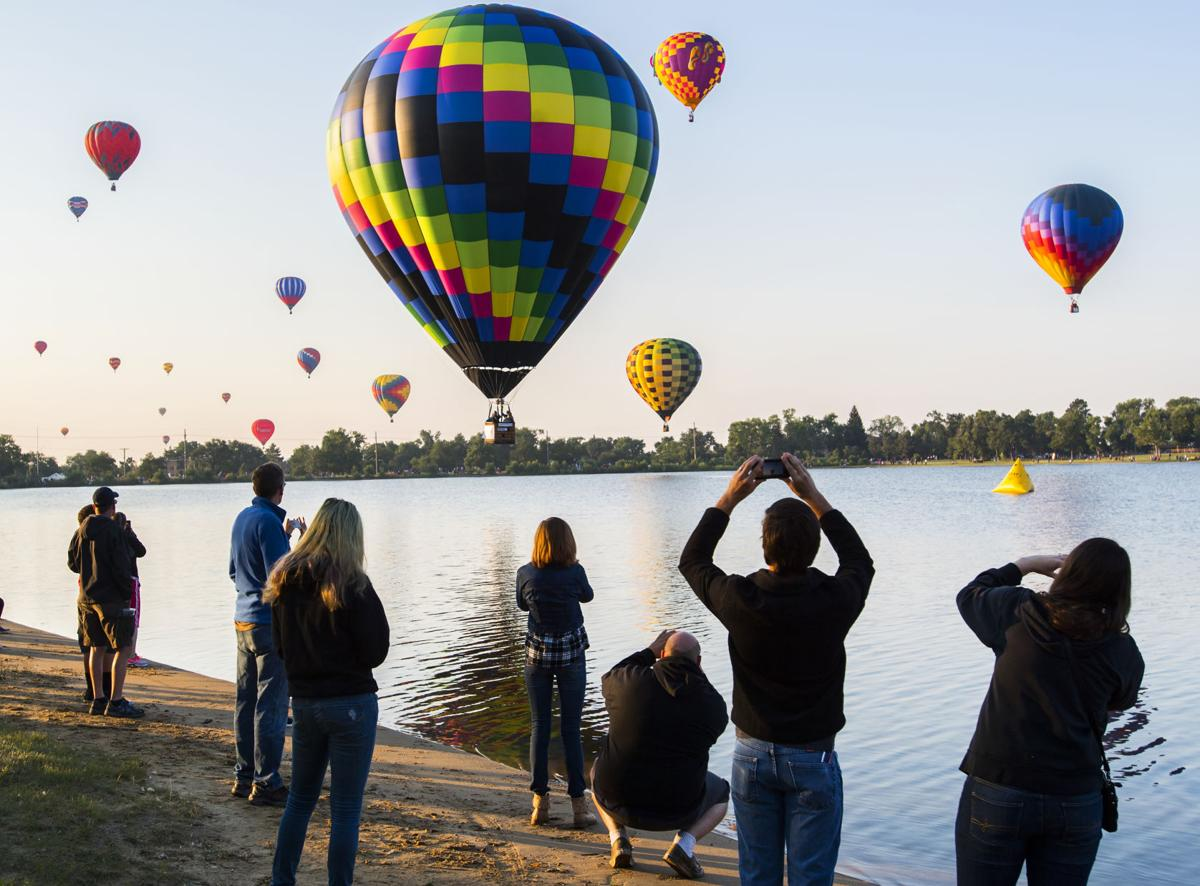 Spectators watch as balloons float over Prospect Lake Saturday, Sept. 2, 2017, during the Colorado Springs Labor Day Lift Off in Memorial Park. The balloon festival runs through Monday morning. (The Gazette, Christian Murdock)