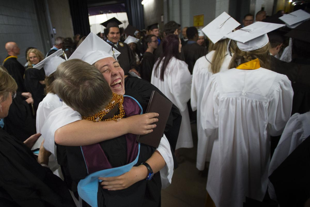 Gretchen Gaebler hugs IB coordinator Steve Kern after the Palmer Class of 2017 graduation ceremony Tuesday, May 23, 2017, at the Boardmoor World Arena in Colorado Springs. The International Baccalaureate students during the ceremony decorated Kern, who loves New Orleans, with Mardi Gras beads to show their appreciation for him. (The Gazette, Christian Murdock)