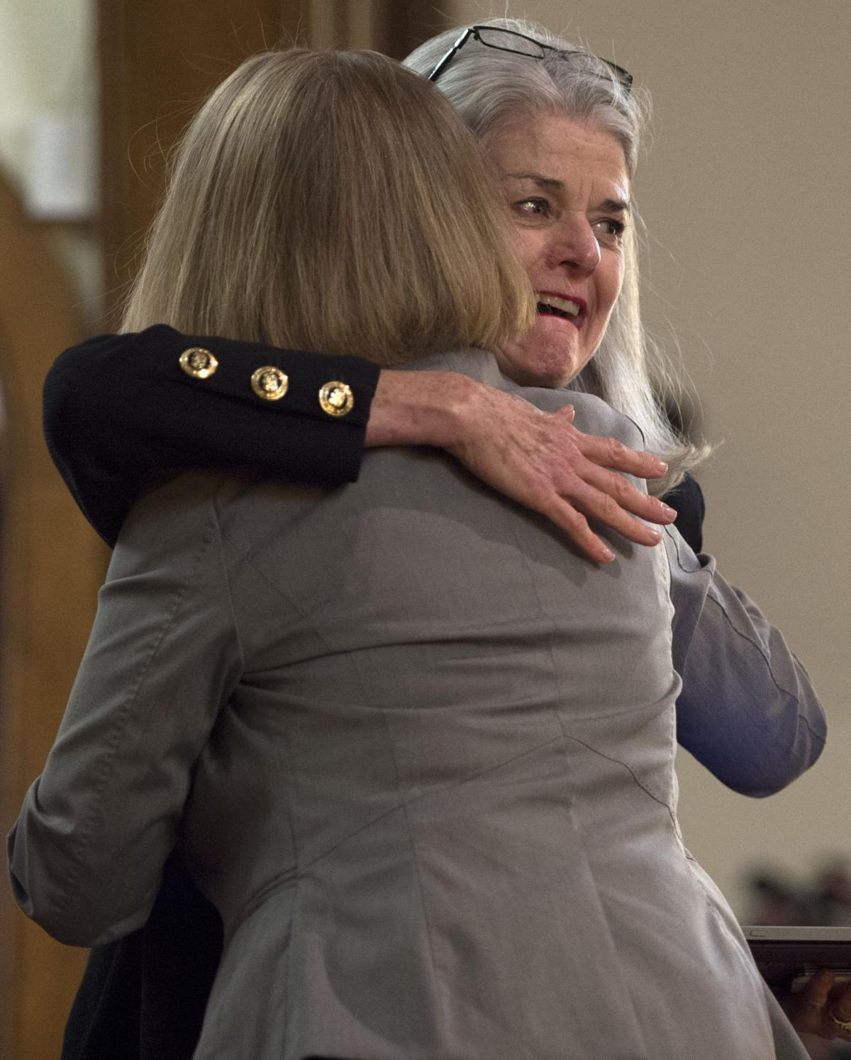 Vicki Cowart, the president and CEO of Planned Parenthood of the Rocky Mountians, receives a hug from Rev. Nori Rost before speaking Saturday, Nov. 28, 2015, during a vigil at the All Souls Unitarian Universalist Church in downtown Colorado Springs for the three killed in the shooting at the Planned Parenthood clinic Friday, Nov. 27, 2015. (The Gazette, Christian Murdock)