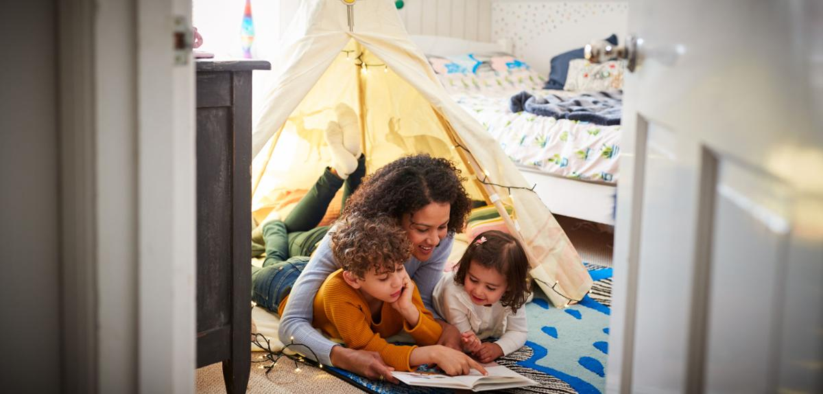 Single Mother Reading With Son And Daughter In Den In Bedroom At Home