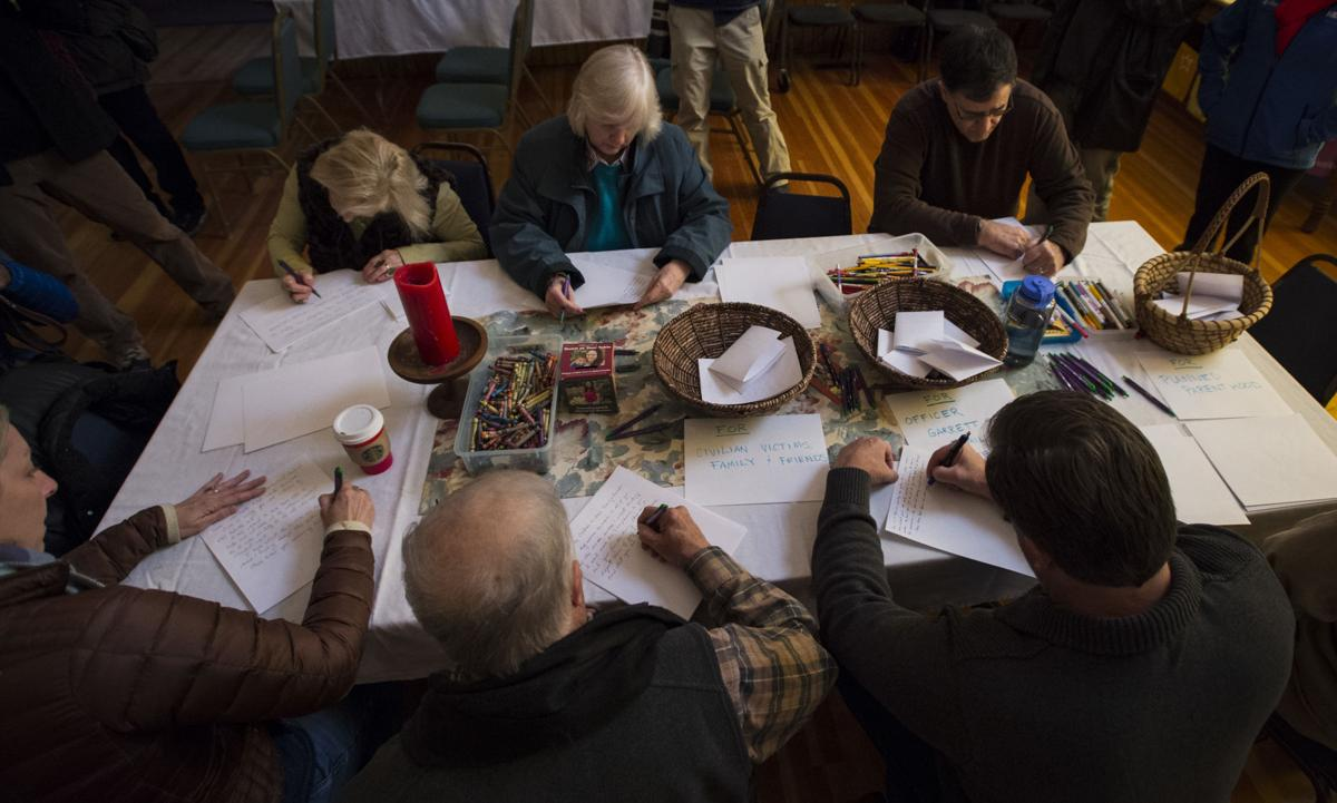 Mourners write letters to the families of the victims Saturday, Nov. 28, 2015, during a vigil at the All Souls Unitarian Universalist Church in downtown Colorado Springs for the three killed in the shooting at the Planned Parenthood clinic Friday, Nov. 27, 2015. (The Gazette, Christian Murdock)