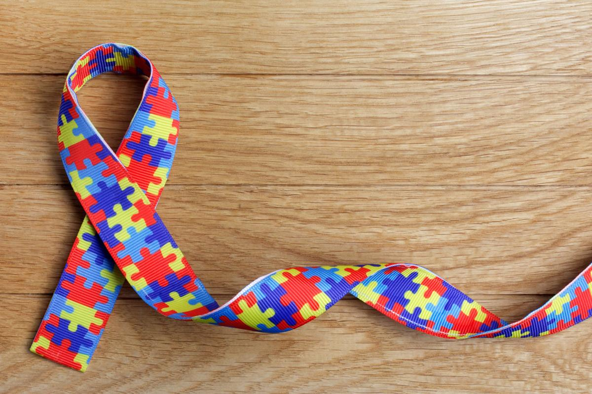 World Autism awareness and pride day or month with Puzzle pattern ribbon on wooden background.