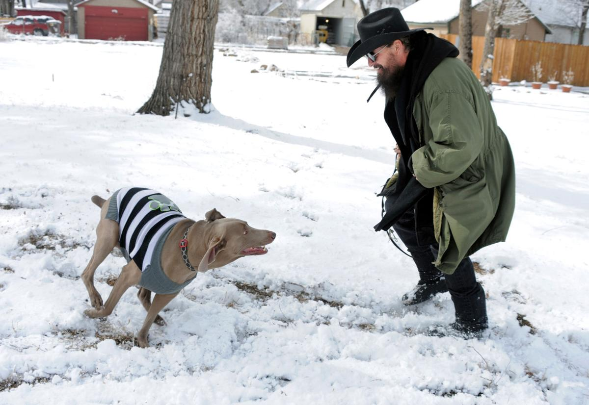 Dan Murray plays with his six-year-old Weimaraner, Bella, in an open lot off West Colorado Avenue near 14th Street Thursday morning. A quick moving  burst of heavy snowfall left the city covered in a blanket of snow. It was Bella's first time playing in the snow after living in warmer southern states and she loved it. Murray says he loves it too after retiring here. Snow showers are possible again Friday for the Pikes Peak Region, accompanied by cooler temperatures, with a forcasted high of near thirty degrees. Carol Lawrence. The Gazette
