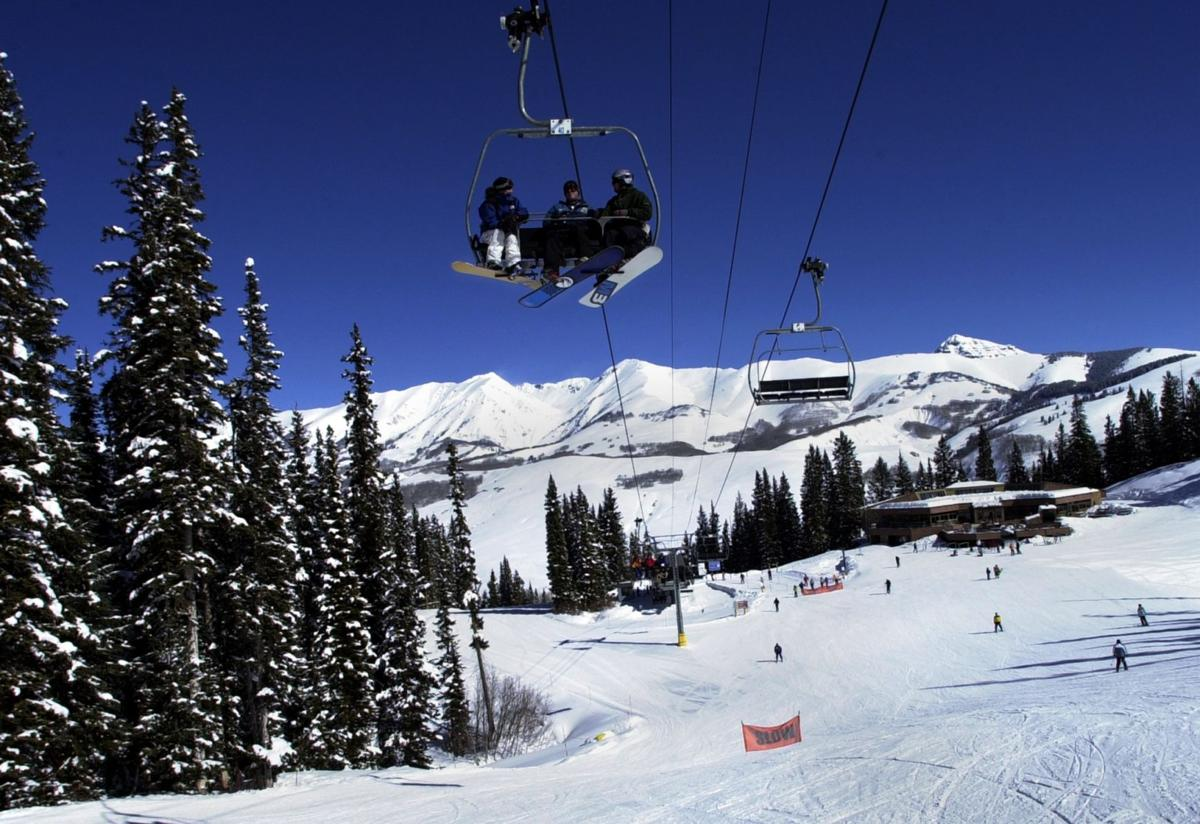 Snowboarders ride the Paradise Lift at Crested Butte Mountain Resort Sunday, March 2, 2003. The lift is one of three high-speed quad lifts at the ski area. At the bottom of the Paradise lift lies the Paradise Warming House where skiers and snowboarders can enjoy a warm meal or bask in the Colorado sun. Photo by Christian Murdock