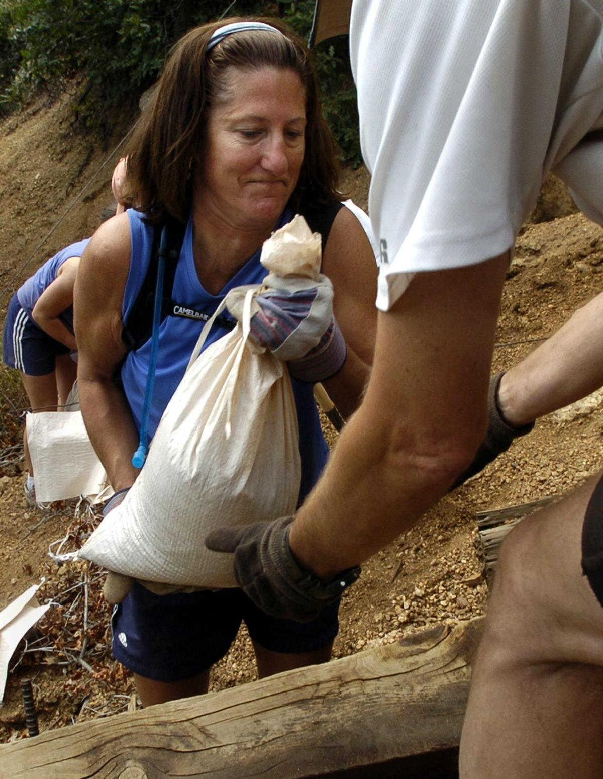 Laura Ryan hands a full bag of sand to David Wall while Caroline Williams fills another one in the background while working on the Incline Trail to the top of Mount Manitou in Manitou Springs, Colo., Saturday, Sept. 10, 2005. The volunteers were using the sandbags to help stop the erosion along the trail from the summer storms. Photo by Christian Murdock/The Gazette
