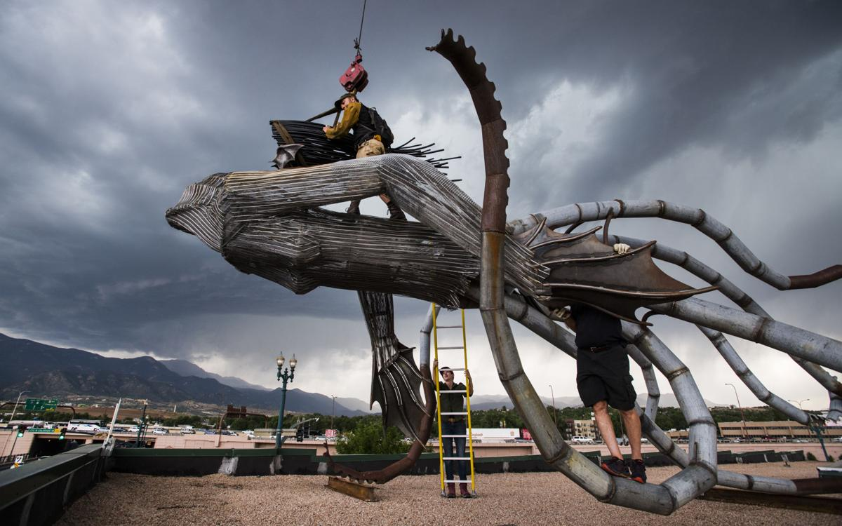 "Fort Collins artist Trace O'Connor attaches the hair of his installation ""Iscariot"" in place after a crane lifted the giant mermaid octopus to the top of the 234 W Colorado Ave. building Thursday, June 7, 2018. The art piece created by recycled metal and wood is part of the 20th anniversary of the Art on the Streets project in downtown Colorado Springs. O'Conner spent about four hours welding the pieces of together before lifting it into place. See gazette.com for a photo gallery.  (The Gazette, Christian Murdock)"