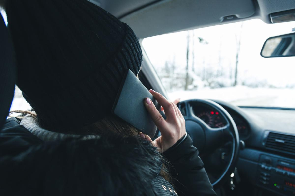 Woman using cell phone while driving