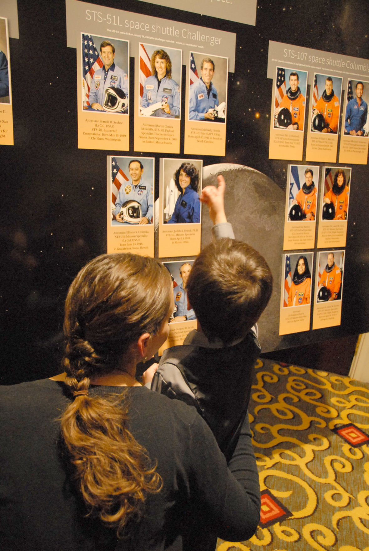 John Applegate, with his mother, Katherine, looks at a display honoring the 14 Space Shuttle and 3 Apollo astronauts who died in space flight. The display was part of the 30th anniversary of the Challenger Shuttle explosion. 012816 Photo by Jeff McCutcheon courtesy of Challenger Learning Center