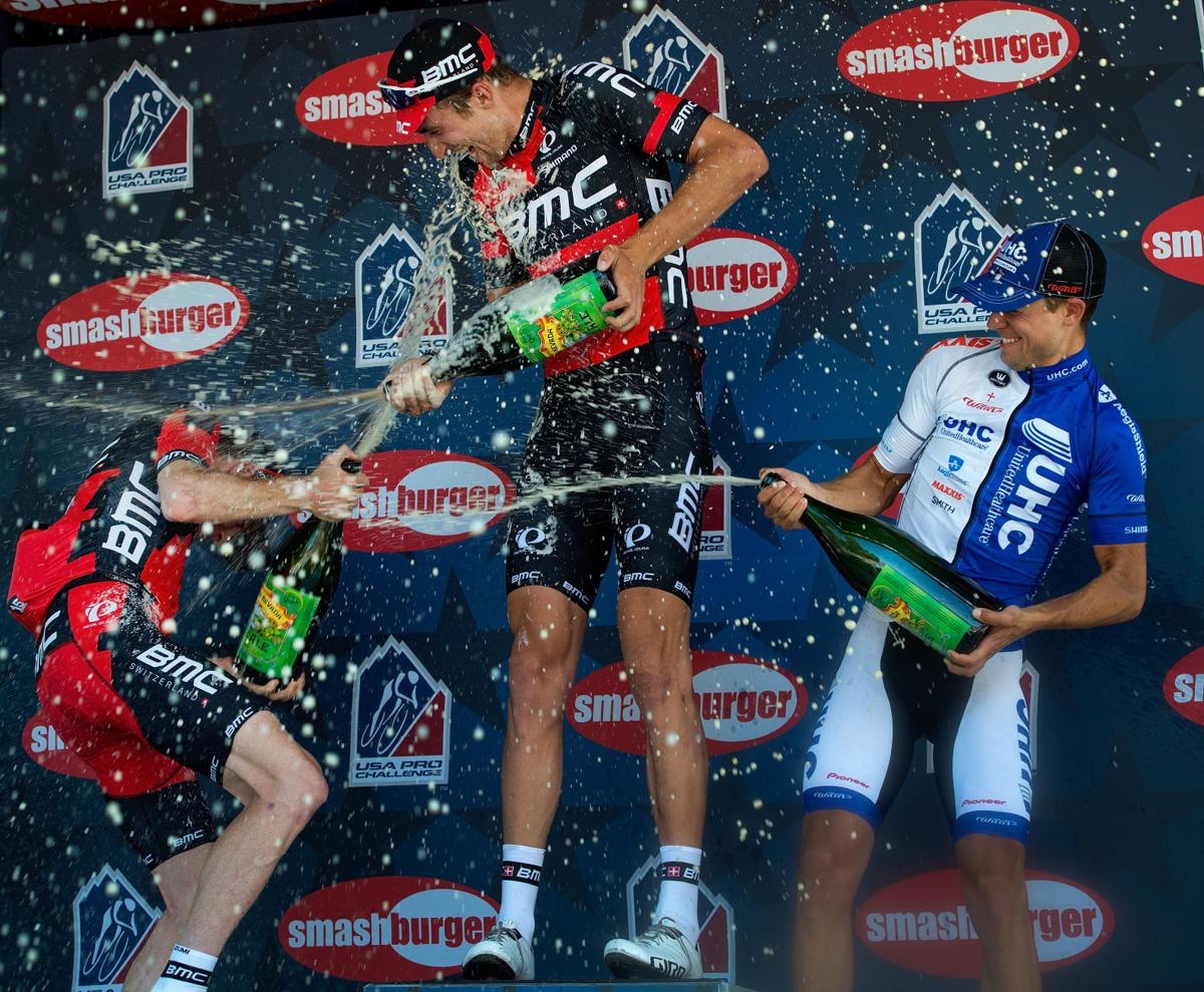BMC Racing's Taylor Phinney of Boulder, Colo., celebrates with beer on the podium with teammate Brent Bookwalter, left, who finished third and United Healthcare's Kiel Reijnenk, who finished second Monday, Aug. 17, 2015, during Stage 1 of the 2015 USA Pro Challenge in Steamboat Springs, Colo. Stage 1 is a two-lap, 97 miles circuit beginning and ending in Steamboat Springs. (The Gazette, Christian Murdock)