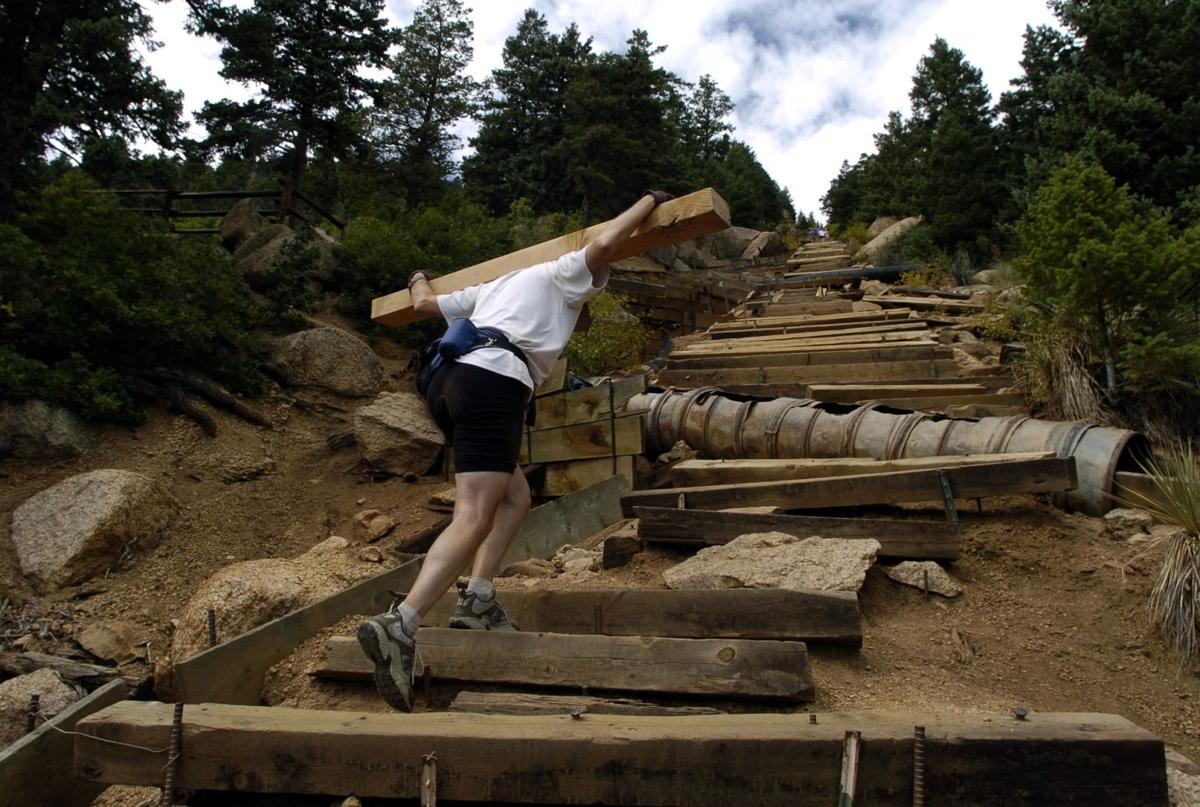 David Wall carries a landscaping timber up the Icline Trail to use as a step on the trail to the top of Mount Manitou Saturday, Sept. 10, 2005. The Incline, with an average grade of 41 percent, makes for an ideal training route for local athletes, but requires year-round maintenance. Photo by Christian Murdock/The Gazette