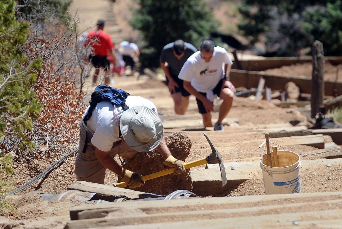 Charles Lindsey shores up a sliding railroad tie Friday, April 8, 2011, on the Manitou Incline while a steady stream of hikers climb the popular trail. ( The Gazette, Christian Murdock)
