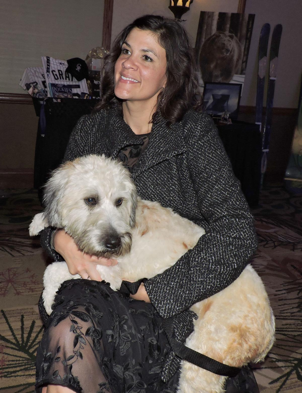 National Mill Dog Rescue volunteer Amber Sathre cuddles Fantasia, who had been rescued two weeks before the benefit gala and was a bit jumpy because she had never been outside a cage.