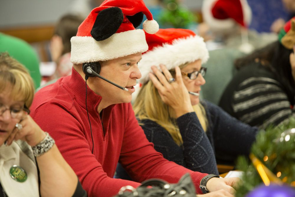 Volunteers answer phones during NORAD Tracks Santa event