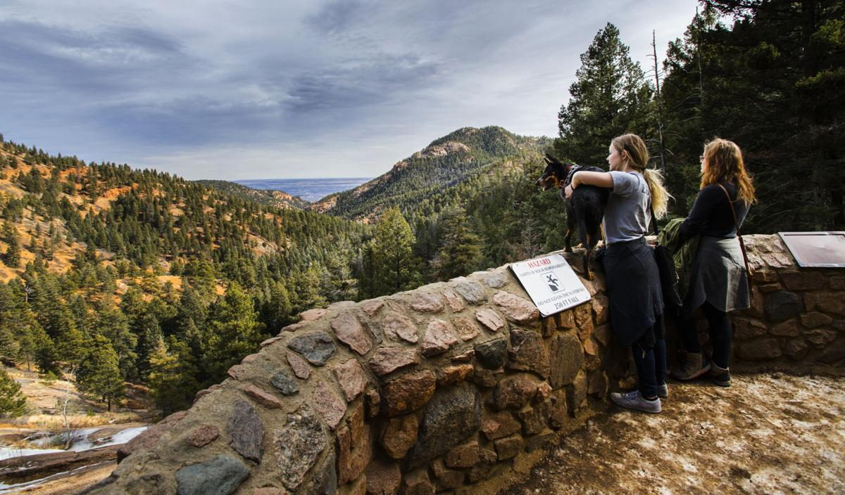 Jesse Smith holds her dog, Jackson, on the ledge of the Helen Hunt Falls overlook so he can see the view of North Cheyenne Cañon Friday, Jan. 19, 2018, while Smith was giving her sister, Cheyenne Smith, right, a tour of the Colorado Springs area. Jesse moved to the Colorado Springs about six months ago from Milwaukee, Wis., and was giving her sister a tour of Colorado. They planned on visiting Estes Park and the Stanley Hotel over the weekend. (The Gazette, Christian Murdock)