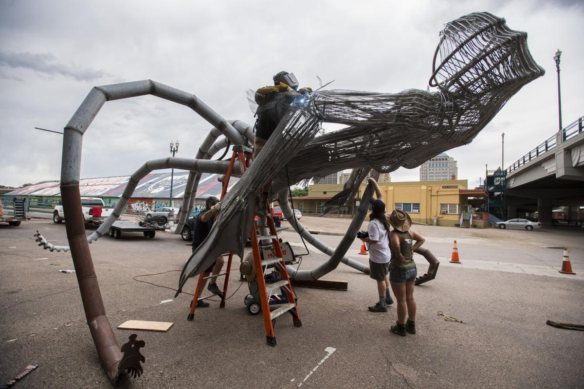 "Fort Collins artist Trace O'Connor welds together his installation ""Iscariot"" before a crane lifted the giant mermaid octopus to the top of the 234 W Colorado Ave. building Thursday, June 7, 2018. The art piece created by recycled metal and wood is part of the 20th anniversary of the Art on the Streets project in downtown Colorado Springs. O'Conner spent about four hours welding the pieces of together before lifting it into place. (The Gazette, Christian Murdock)"
