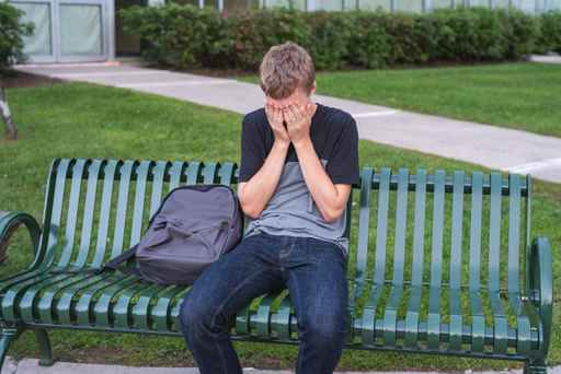 Upset teenager sitting on a bench all alone.