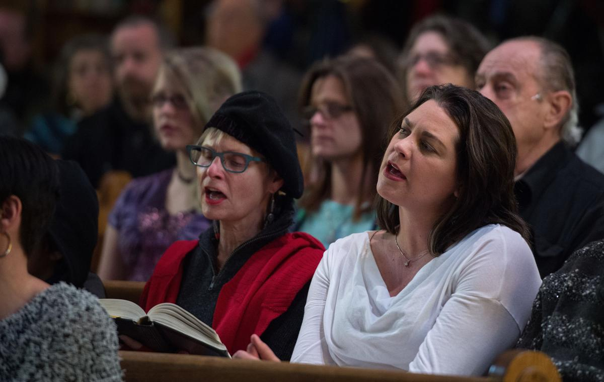 """Lynn Young, left, and Deb Walker sing along to """"Amazing Grace"""" Saturday, Nov. 28, 2015, during a vigil at the All Souls Unitarian Universalist Church in downtown Colorado Springs for the three killed in the shooting at the Planned Parenthood clinic Friday, Nov. 27, 2015. (The Gazette, Christian Murdock)"""
