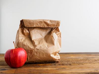 Papiertüte mit Pausenbrot und ein roter Apfel