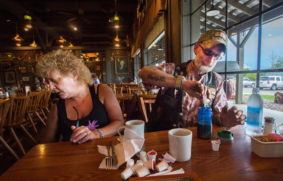 Jerrald Jensen pours his coffee and cream into a sippy cup while eating at a Colorado Springs restaurant with his wife, Robin, Tuesday, Aug. 25, 2015. Jensen has trouble drinking from a normal cup without teeth and goes through a stack of napkins trying to eat a meal without making a mess. He has a titanium jaw and is still toothless from the roadside bomb that blew off parts of his face in 2007. (The Gazette, Christian Murdock)