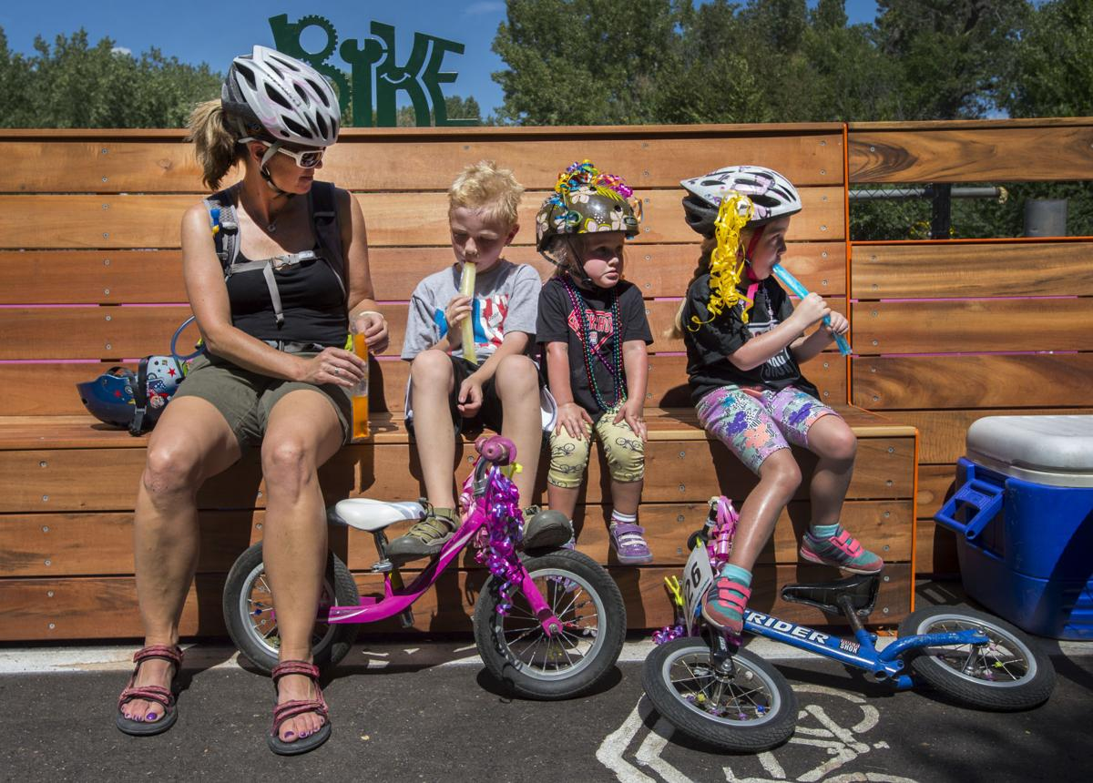 Liz Hunt, left, Ian Hunt, 7; Skyler Watt, 3, and Kaiya Watt, 5, rest on the new Popcycle Bridge's benches and enjoy a popcycle Sunday, Aug. 30, 2015, while riding to The Great Bicycle Carnival in Monument Valley Park. The Great Bicycle Carnival celebrated the 10th anniversary of Kids on Bikes and the opening of the Popcycle Bridge along the Pikes Peak Greenway Trail just north of Monument Valley Park. (The Gazette, Christian Murdock)