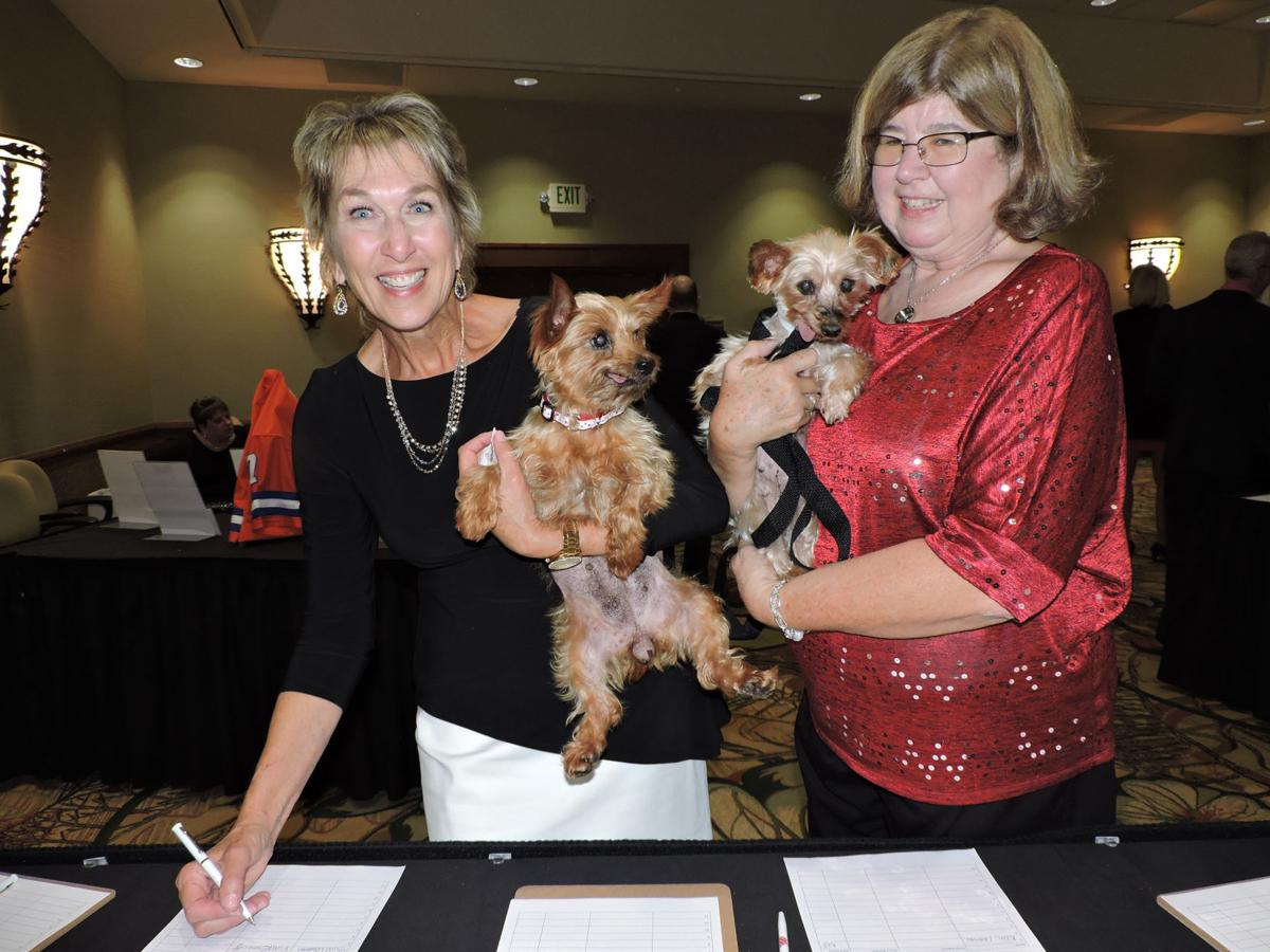 National Mill Dog Rescue benefit gala: Volunteers Kim Lehmann, left, with Lucy, and Sandy Alton, with Gracie, visit the silent auction table. 101417 Photo by Linda Navarro