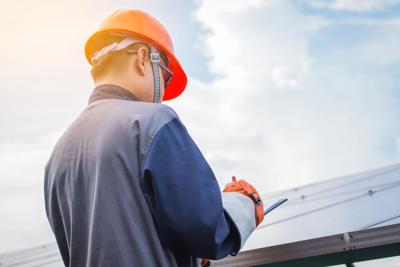 engineers operating and check generating power of solar power plant on solar rooftop; technician in industry uniform on level of job description at industrial