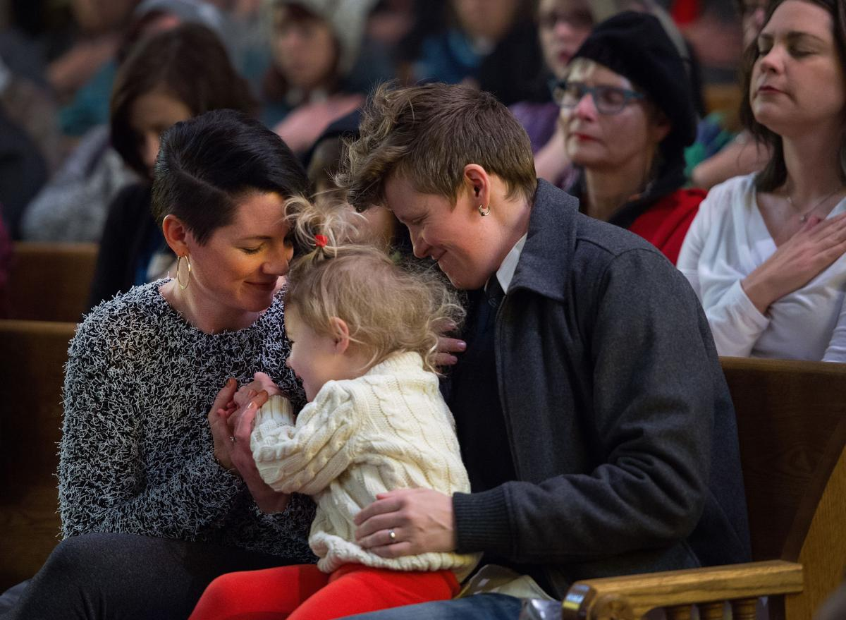Erika Musick, left, and Sarah Musick play with their daughter, Wren, 2, Saturday, Nov. 28, 2015, during a vigil at the All Souls Unitarian Universalist Church in downtown Colorado Springs for the three killed in the shooting at the Planned Parenthood clinic Friday, Nov. 27, 2015. (The Gazette, Christian Murdock)