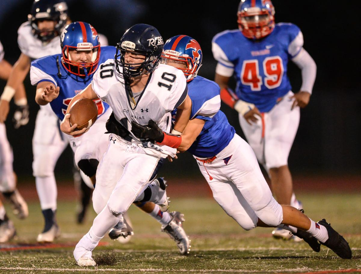 Columbine's Jake Lowry (center) is brought down by Fountain-Fort Carson's Nico MacDonald (right) on Friday, August 28, 2015 at Fountain-Fort Carson High School. Photo by Spotlight Sports Photography