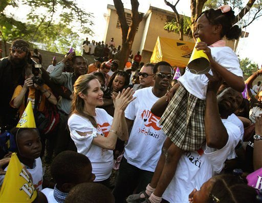 FILE - In this Jan. 13, 2006, file photo, actress Angelina Jolie claps her hands as Haitian-born hip-hop musician Wyclef Jean lifts a schoolgirl up in the air, during the first anniversary party for his charity Yele Haiti, at Telemax, a local TV station o