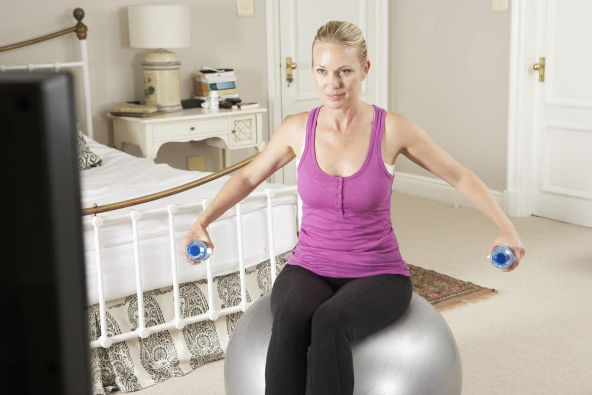 Woman Exercising Whilst Watching Fitness DVD On Television