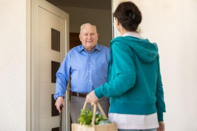 Home caregiver – woman helping senior man
