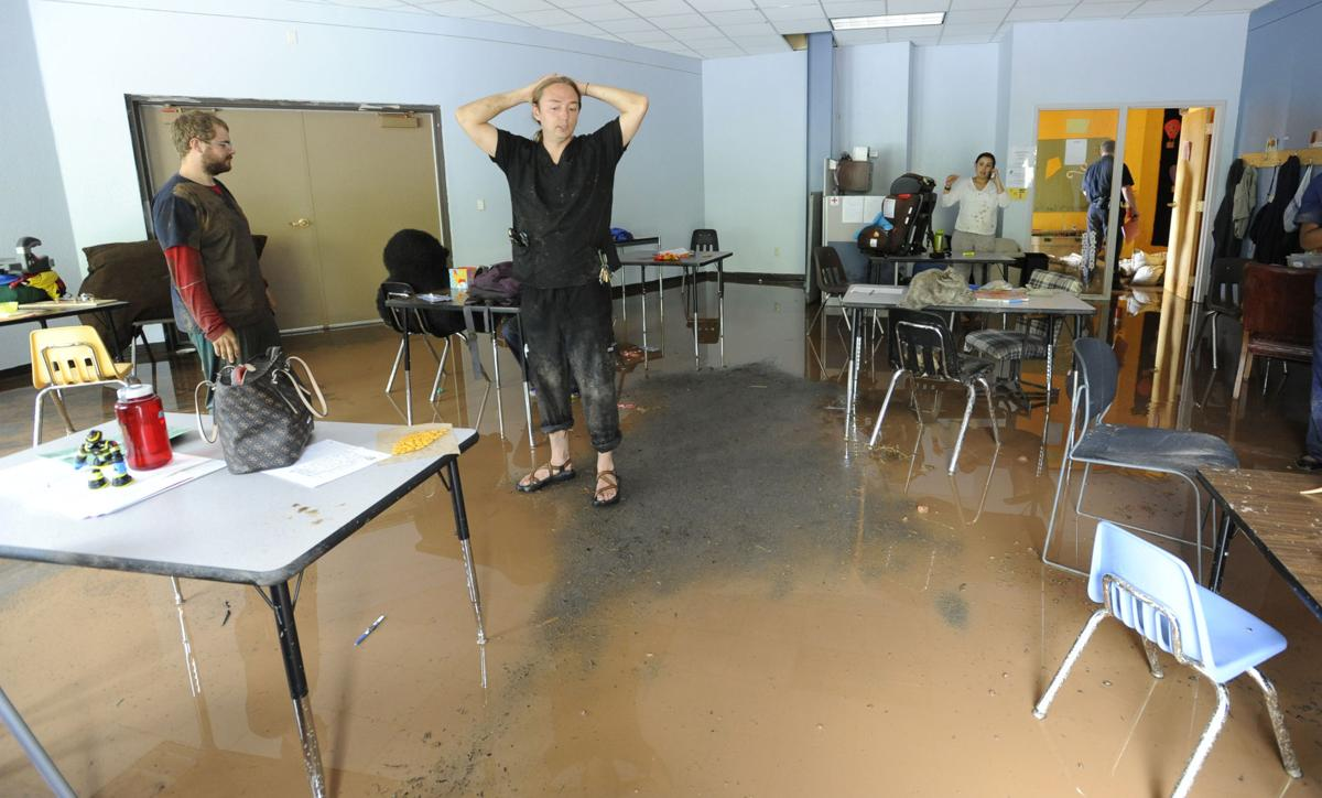 Therapist Jacob Cox looks around a flooded classroom at the Alpine Autism Center in Mountain Shadows on Monday, August 10, 2015. When the building was flooded during the deluge, all the children were safely evacuated, mud and water filled the building. (Jerilee Bennett/The Gazette)