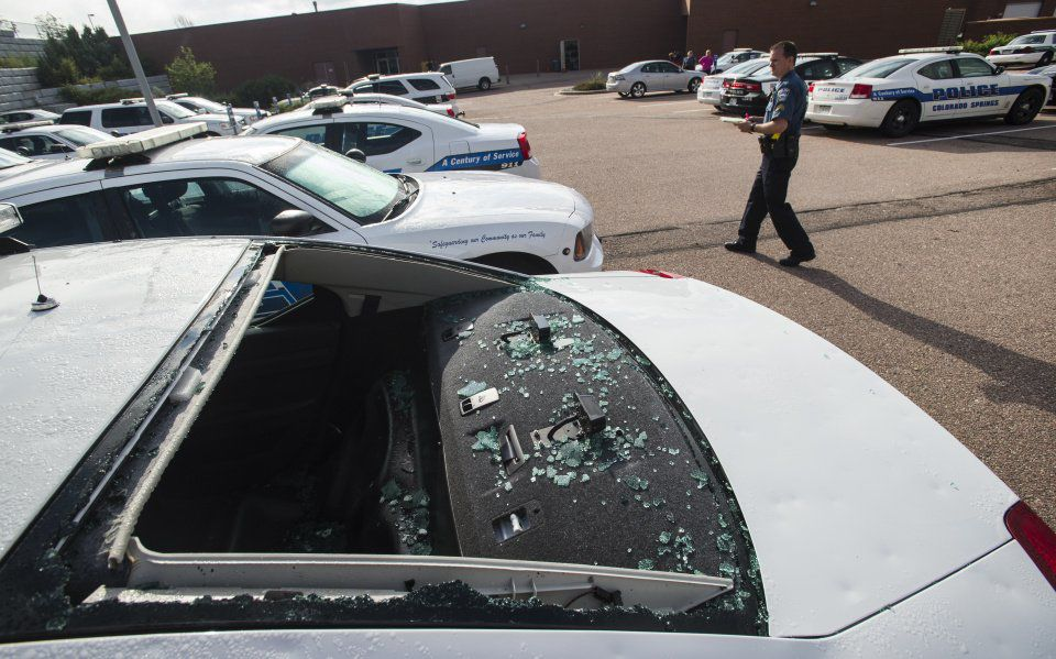 Police Sgt. Kory Dabb accesses the damage to the fleet of police cars at the Stetson Hills police station Friday morning, July 29, 2016, after a Thursday night hail storms damaged more than two dozen vehicles. (The Gazette, Christian Murdock)