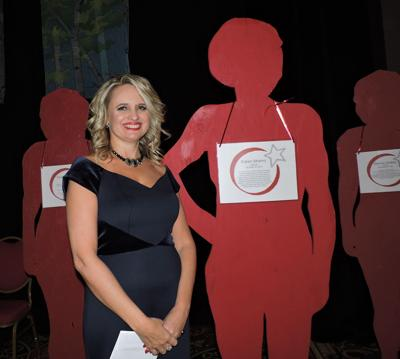 Celebrating 40 Years: TESSA Executive Director SherryLynn Boyles shares the stage with figures representing the 10,000 victims of domestic violence served annually, some of whom lost their fight. 093017 Photo by Linda Navarro